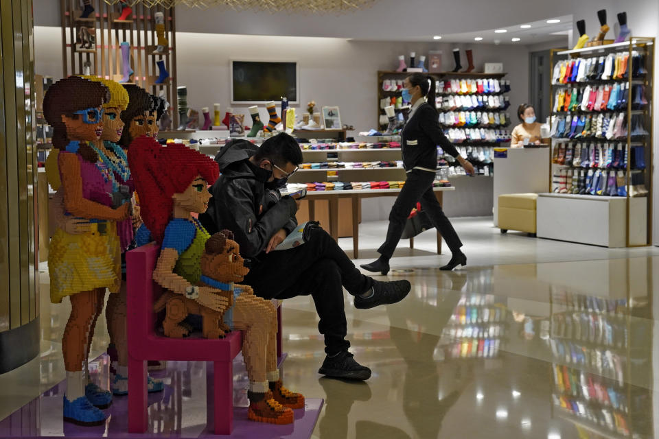 A woman wearing a face mask to help curb the spread of the coronavirus walks by a masked man who sits on a Lego blocks, browsing his smartphone inside a shopping mall in Beijing, Tuesday, Nov. 24, 2020. China has reported new coronavirus cases in the cities of Shanghai and Tianjin as it seeks to prevent small outbreaks from becoming larger ones. (AP Photo/Andy Wong)