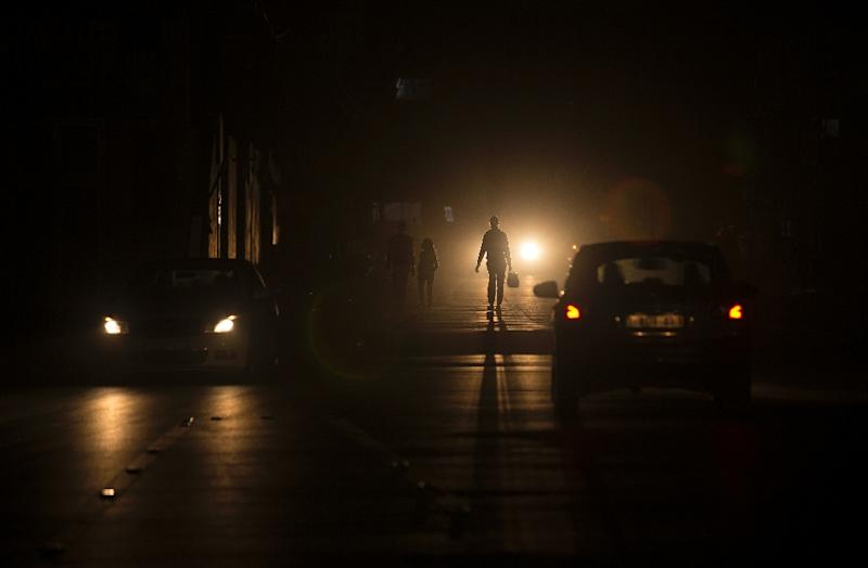 Palestinians walk on a street at the Al-Shati refugee camp in Gaza City during a power outage on June 11, 2017 (AFP Photo/MAHMUD HAMS)