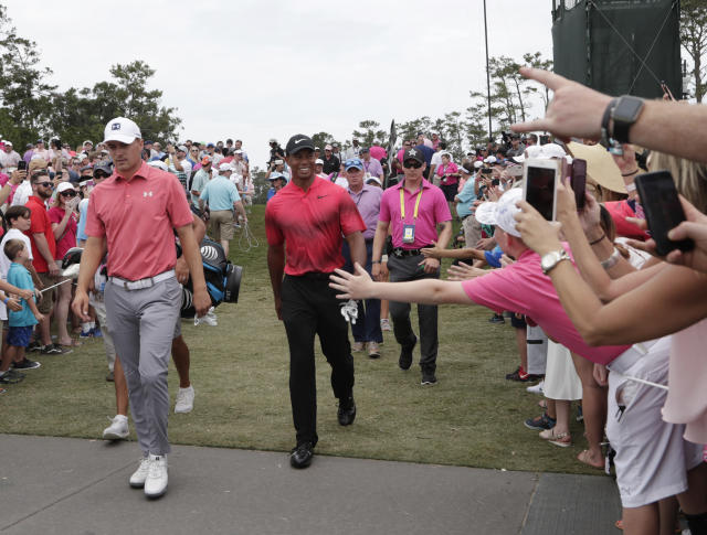 Fans cheer as Tiger Woods and Jordan Spieth head to the second tee, during the final round of The Players Championship golf tournament, Sunday, May 13, 2018, in Ponte Vedra Beach, Fla. (AP Photo/Lynne Sladky)