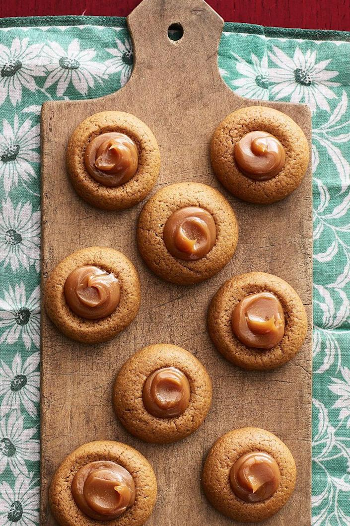 """<p>Dulce de leche is a creamy caramelized milk that makes these cookies extra decadent, but if you can't find it at your local grocery store, you can also use caramel sauce. </p><p><a href=""""https://www.thepioneerwoman.com/food-cooking/recipes/a34128896/gingerbread-thumbprint-cookies-with-dulce-de-leche-recipe/"""" rel=""""nofollow noopener"""" target=""""_blank"""" data-ylk=""""slk:Get Ree's recipe."""" class=""""link rapid-noclick-resp""""><strong>Get Ree's recipe.</strong></a></p>"""