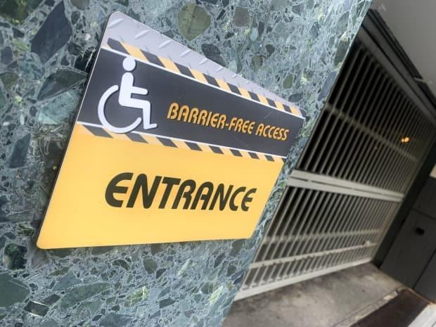 An accessibility access point for a building through a parking garage in downtown Vancouver. It is behind a locked gate and has a grate that is difficult to cross with a wheelchair.  (David Horemans/CBC - image credit)