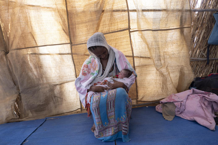 "Lemlem Gebrehiwet, a 20-year-old Tigrayan refugee, holds her 3-day-old daughter, Semhal, in their shelter in Hamdayet, eastern Sudan, near the border with Ethiopia, on March 16, 2021. Other Tigrayans were turned away because of who they were. ""They started distributing new ID cards in Bahkar but only for Amhara and Wolkait,"" said Gebrehiwet, who fled while heavily pregnant and gave birth three days after reaching Sudan. (AP Photo/Nariman El-Mofty)"