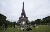 """People relax at the Champ-de-Mars garden next to the Eiffel Tower in Paris, Friday, July 16, 2021. The Eiffel Tower is reopening Friday for the first time in nine months, just as France faces new virus rules aimed at taming the fast-spreading delta variant. The """"Iron Lady"""" was ordered shut in October as France battled its second surge of the virus. (AP Photo/Michel Euler)"""
