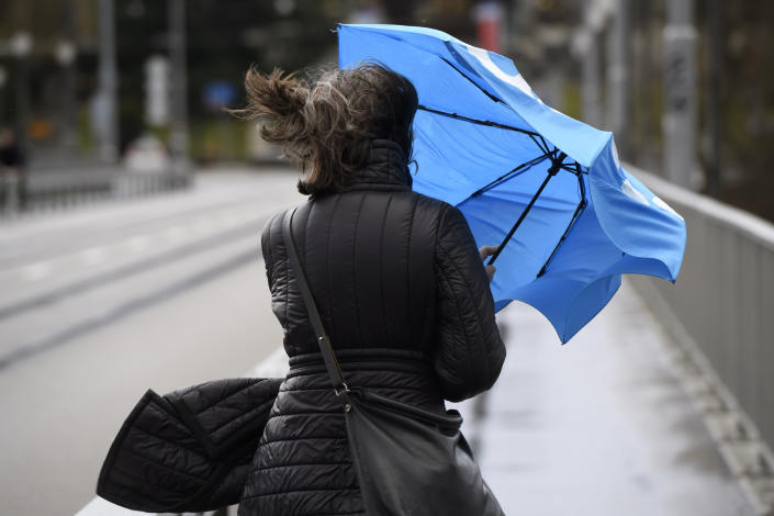 A woman with an umbrella walks on a road during stormy weather in Bern, Switzerland, Monday, Feb. 10, 2020. A storm battered the U.K. and northern Europe with hurricane-force winds and heavy rains Sunday, halting flights and trains and producing heaving seas that closed down ports. Soccer games, farmers' markets and cultural events were canceled as authorities urged millions of people to stay indoors, away from falling tree branches. (Anthony Anex/Keystone via AP)