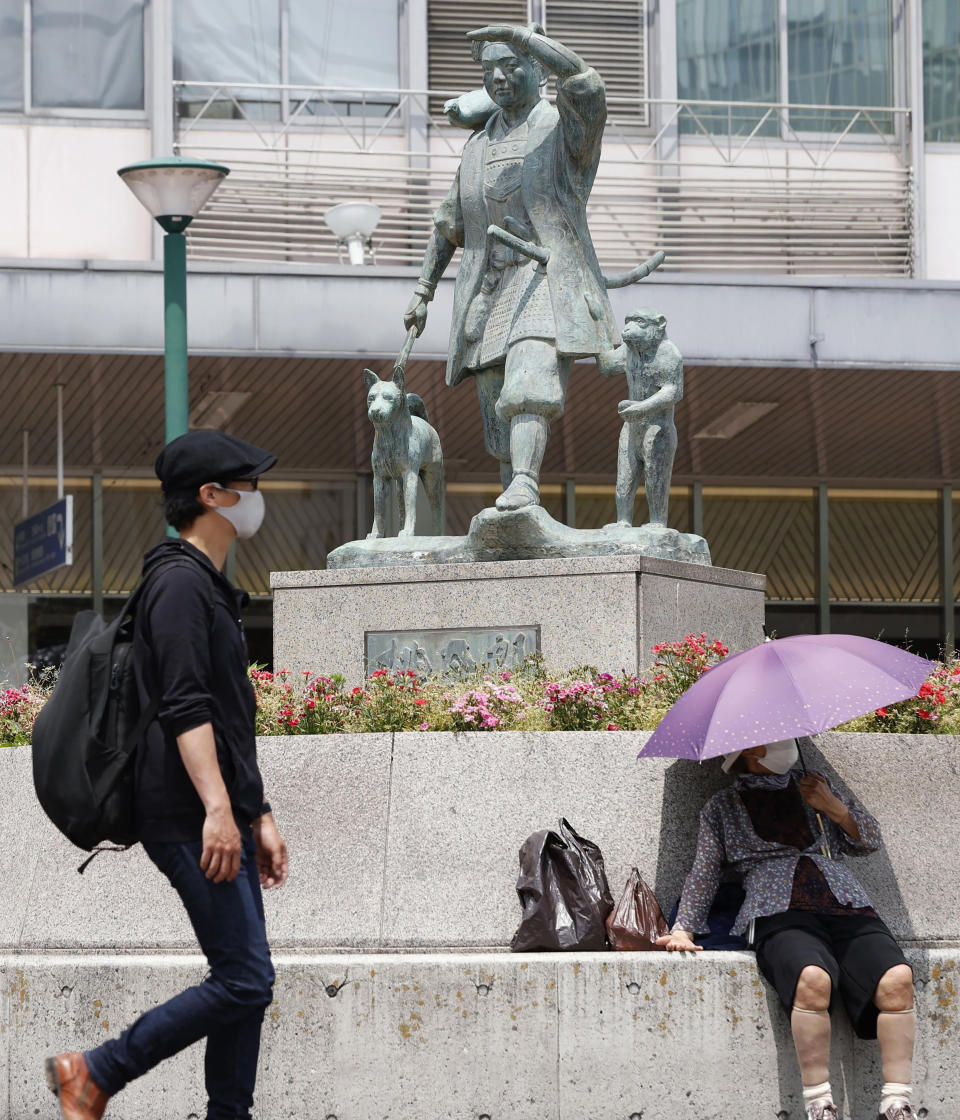People wear face masks to help curb the spread of the coronavirus in front of Okayama railway station in Okayama, western Japan, Friday, May 14, 2021. Japan is set to further expand a coronavirus state of emergency, currently in Tokyo and five other prefectures, to nine areas, including Okayama, as the government is determined to hold the Olympics in just over two months. (Kyodo News via AP)