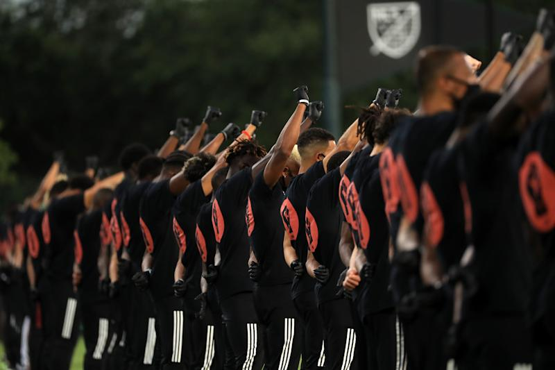 MLS players raise their fists in solidarity with Black Lives Matter before Wednesday's match between Orlando City and Inter Miami in Florida