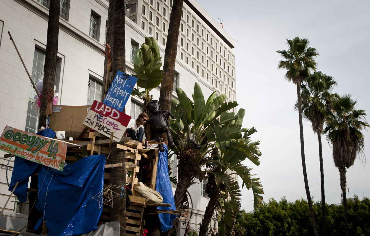 An Occupy Los Angeles supporter sits in a tree house at the demonstration's encampment in front of Los Angeles City Hall, Monday, Nov. 28, 2011, in Los Angeles. Los Angeles Mayor Antonio Villaraigosa stated Friday that the protestors's campsite will be dismantled, beginning at 12:01 a.m. Monday. (AP Photo/Bret Hartman)