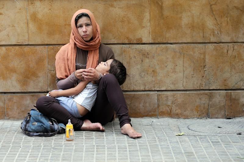 A Syrian refugee woman begs for money on the pavement of a street in the Lebanese capital Beirut on July 9, 2015 (AFP Photo/Joseph Eid)