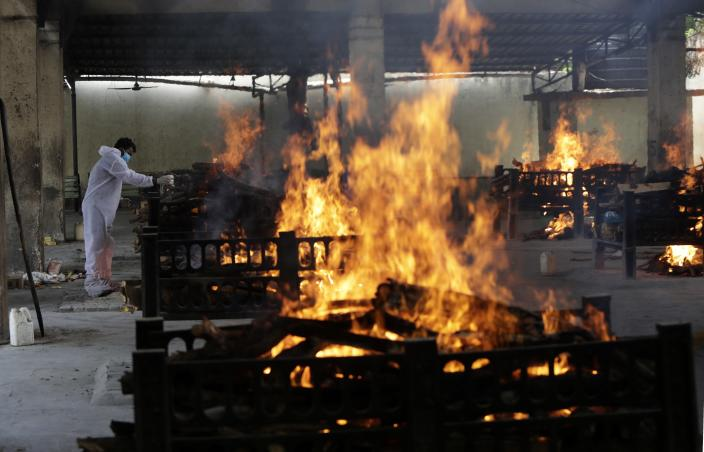 Flames rise from cremation pyres of 13 COVID-19 patients who died in a fire that broke out in Vijay Vallabh COVID-19 hospital, at Virar, near Mumbai, India, Friday, April 23, 2021. Delhi has been cremating so many bodies of coronavirus victims that authorities are getting requests to start cutting down trees in city parks, as a second record surge has brought India's tattered healthcare system to its knees. (AP Photo/Rajanish Kakade)