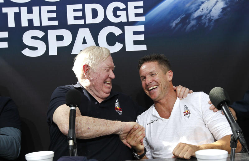 Felix Baumgartner, right, of Austria, shares a laugh with Col. Joe Kittinger, USAF retired, after successfully jumping from a space capsule lifted by a helium balloon at a height of just over 128,000 feet above the Earth's surface, beating Kittinger's old record of 102,799 ft., Sunday, Oct. 14, 2012, in Roswell, N.M. (AP Photo/Ross D. Franklin)