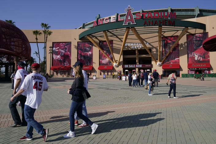Fans walk outside Angel Stadium when a baseball game between the Minnesota Twins and the Los Angeles Angels was postponed Saturday, April 17, 2021, in Anaheim, Calif. MLB said the game was postponed to allow for continued COVID-19 testing and contact tracing involving members of the Twins organization. (AP Photo/Ashley Landis)