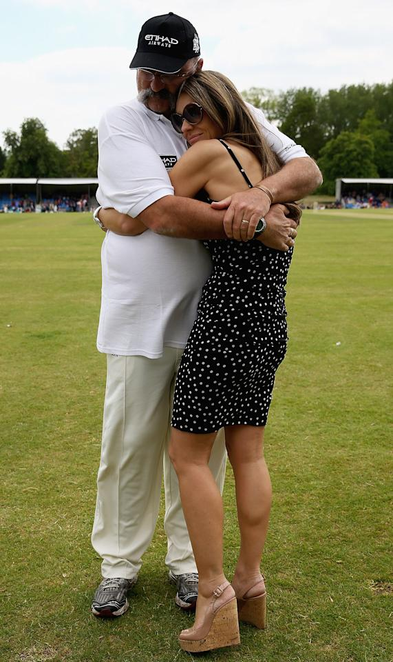 CIRENCESTER, ENGLAND - JUNE 09:  Merv Hughes and Elizabeth Hurley share a cuddle during the Shane Warne's Australia vs Michael Vaughan's England T20 match at Circenster Cricket Club on June 9, 2013 in Cirencester, England.  (Photo by Matthew Lewis/Getty Images)