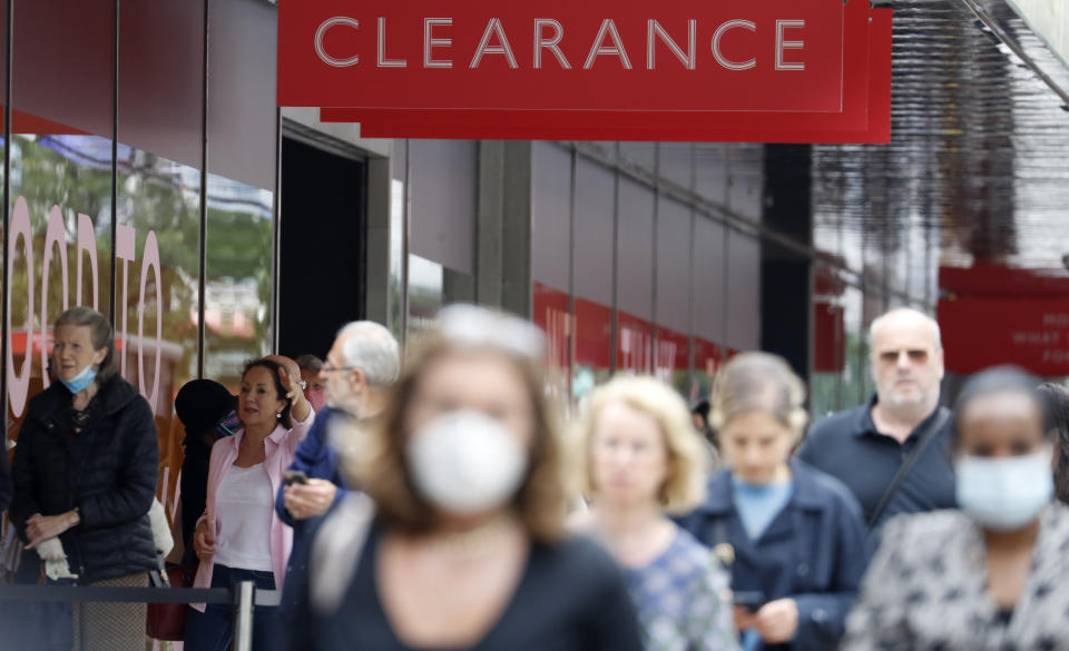 People, some wearing masks queue outside a John Lewis store, in London, Thursday, July 16, 2020. Unemployment across the U.K. has held steady during the coronavirus lockdown as a result of a government salary support scheme, but there are clear signals emerging that job losses will skyrocket over coming months. The Office for National Statistics said Thursday there were 649,000 fewer people, or 2.2%, on payroll in June when compared with March when the lockdown restrictions were imposed. (AP Photo/Alastair Grant)