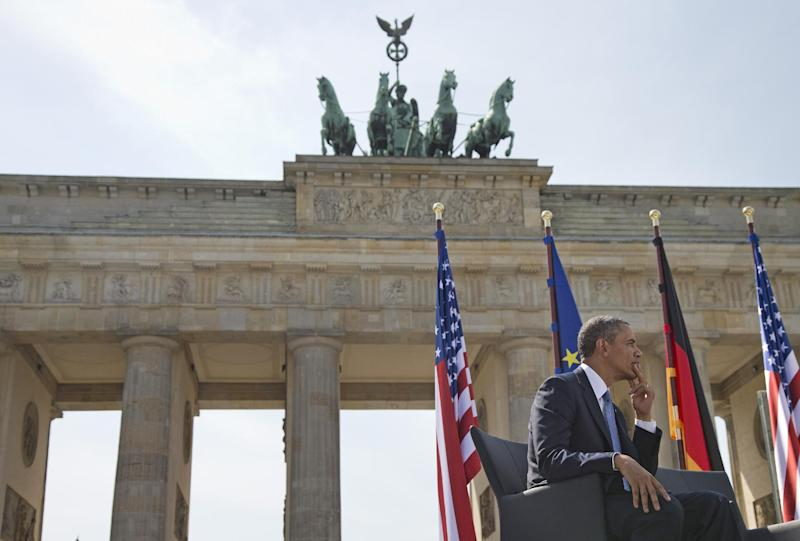 President Barack Obama listens as he is introduced by German Chancellor Angela Merkel before speaking at the Brandenburg Gate in Berlin, Wednesday, June 19, 2013. Obama called to reduce the world's nuclear stockpiles, including a proposed one-third reduction in U.S. and Russian arsenals, a senior administration official said. (AP Photo/Evan Vucci)