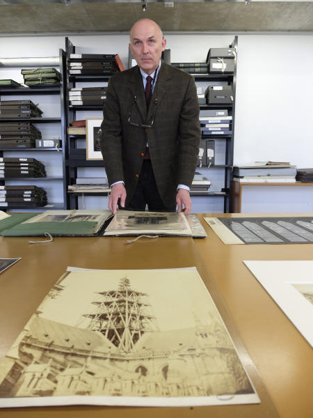 Jean-Charles Forgeret poses with archives documents related to Notre Dame cathedral in Charenton le Pont, outside Paris, Thursday, April 18, 2019. The reconstruction of Paris' Notre Dame Cathedral will rely on part on extensive plans drawn up in the 19th century for its last big renovation. Forgeret noted that the last restoration took 20 years, and cast doubt on the French president's 5-year deadline on fixing Notre Dame this time. (AP Photo/Nicolas Garriga)