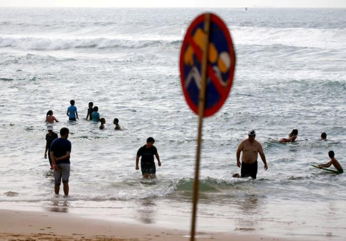 People swim even though bathing is banned on beaches by government directive in order to combat the spread of coronavirus disease (COVID-19), in Umhlanga