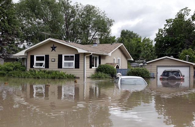 Cars and homes are submerged in flood waters in High River, Alberta, Thursday, June 20, 2013. Calgary city officials say as many as 100,000 people could be forced from their homes due to heavy flooding in western Canada, while mudslides have forced the closure of the Trans-Canada Highway around the mountain resort towns of Banff and Canmore. (AP Photo/The Canadian Press, Jeff McIntosh)