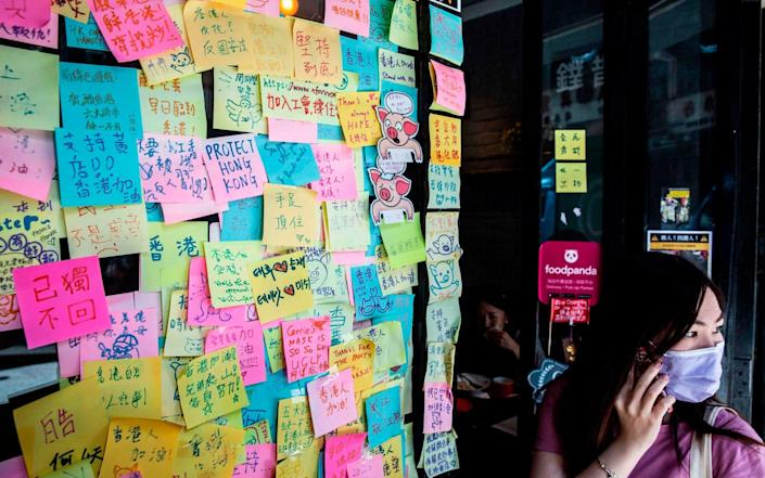 A woman (R) stands next to layers of notes on a Lennon Wall with messages of support for the pro-democracy protests outside a restaurant in Hong Kong - AFP