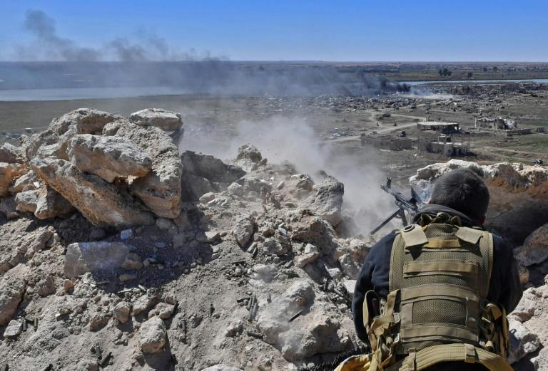 A fighter with the Syrian Democratic Forces opens fire toward a part of Baghouz where remaining Islamic State group fighters are holding out in their last position