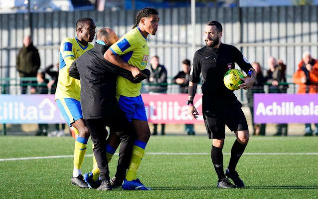 Haringey Borough's Coby Rowe is restrained by staff after racist abuse allegedly directed at one of his team-mates from travelling Yeovil supporters - Pinnacle