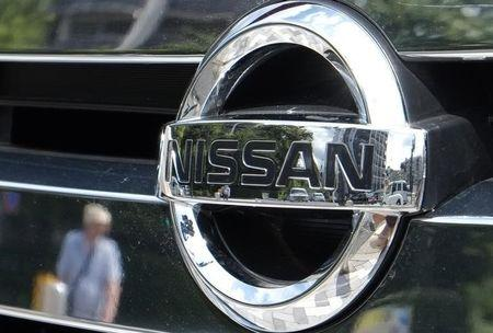 Pedestrian and cars are reflected in a Nissan Motor logo at the company's dealership in Tokyo