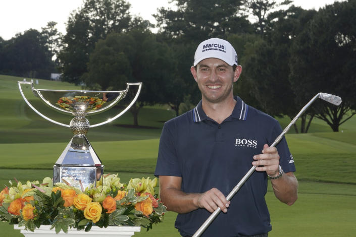 Patrick Cantlay poses with the trophies after winning the Tour Championship golf tournament and the FedEx Cup at East Lake Golf Club, Sunday, Sept. 5, 2021, in Atlanta. (AP Photo/Brynn Anderson)
