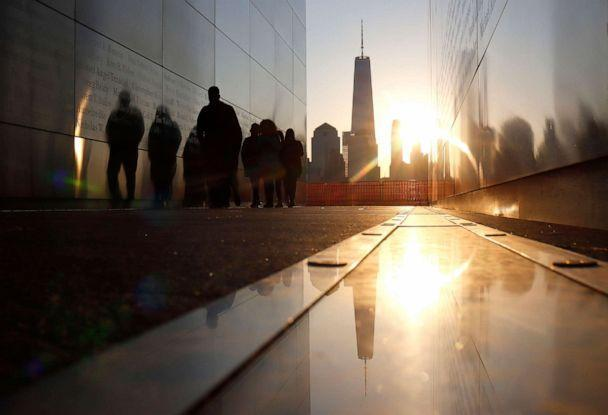 PHOTO: The sun rises behind the skyline of lower Manhattan and One World Trade Center in New York City as people walk through the Empty Sky 9/11 Memorial as seen from Jersey City, N.J., April 24, 2021. (Gary Hershorn/Getty Images, FILE)