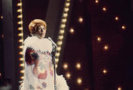 """<p>Aretha Franklin performing live wearing a vibrant orange hairstyle and '70s style """"flower power"""" dress with white feather details around the collar and sleeves. (Photo by ABC via Getty Images) </p>"""