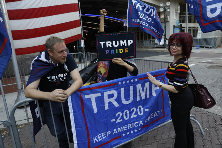 A passerby stops to speak with a few supporters of President Donald Trump protesting outside the Pennsylvania Convention Center, where vote counting continues, in Philadelphia, Monday, Nov. 9, 2020, two days after the 2020 election was called for Democrat Joe Biden. (AP Photo/Rebecca Blackwell)