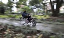 A tourist rides an electric wheelchair during a tour in Medellin, Colombia, Wednesday, Nov. 18, 2020. The steering and breaks on the wheelchairs are like those on a regular bicycle, while accelerating only requires pushing a button on one of the handles. (AP Photo/Fernando Vergara)