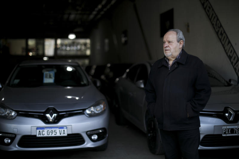 Carlos Avoguarda stands outside his auto shop in Buenos Aires, Argentina, Tuesday, Aug. 13, 2019.  Two days after the overwhelming primary election loss of President Mauricio Macri sent the Argentine peso into a tailspin, not a single customer has walked through the door. (AP Photo/Natacha Pisarenko)