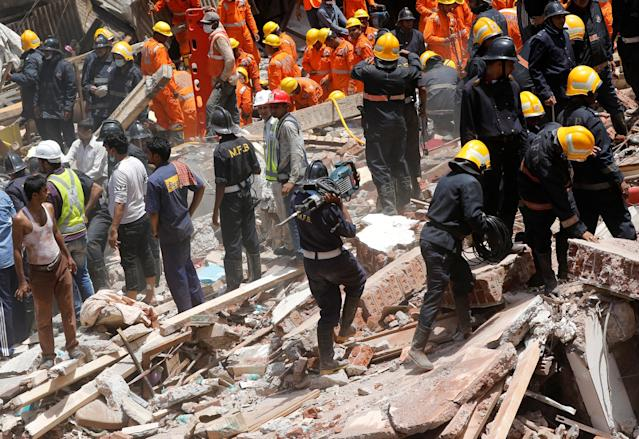 <p>A firefighter arrives with a jackhammer during a search for survivors at the site of a collapsed building in Mumbai, India, Aug. 31, 2017. (Photo: Shailesh Andrade/Reuters) </p>