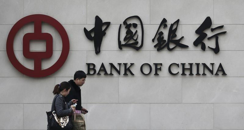 Pedestrians walk past a Bank of China sign at its branch in Beijing