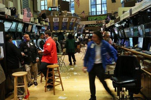 <p>Traders work on the floor of the New York Stock Exchange on July 6 in New York City. Markets braced for the start of the US corporate earnings season Monday, with analysts expecting lackluster profits, underscoring misgivings about the state of the broader global economy.</p>