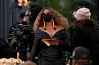 """<p>Wearing a <a href=""""https://www.popsugar.com/fashion/beyonce-leather-dress-at-2021-grammys-48216692"""" class=""""link rapid-noclick-resp"""" rel=""""nofollow noopener"""" target=""""_blank"""" data-ylk=""""slk:Schiaparelli dress"""">Schiaparelli dress</a> with a matching mask and Jimmy Choo shoes.</p>"""