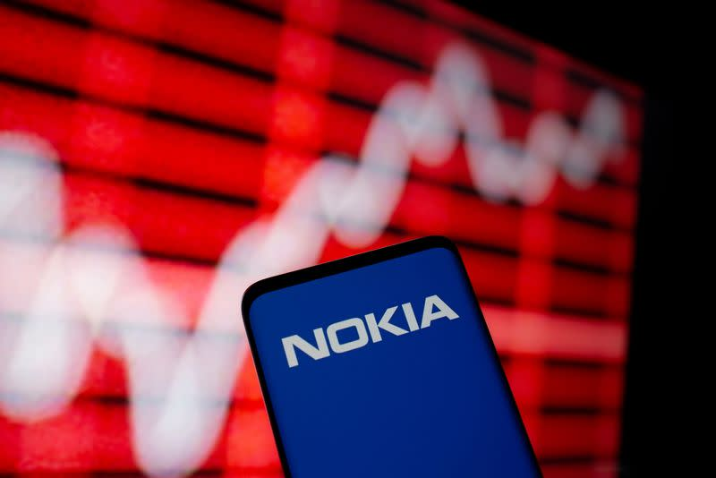 FILE PHOTO: The Nokia logo is seen on a smartphone in front of a displayed stock graph in this illustration