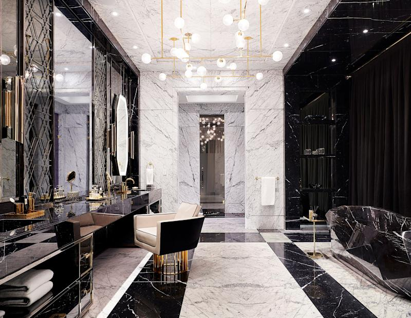 The master bath features a Nero Marquina marble vanity and tub. Custom chandelier by Lumifer; Brabbu sconces; chair by Rafauli.