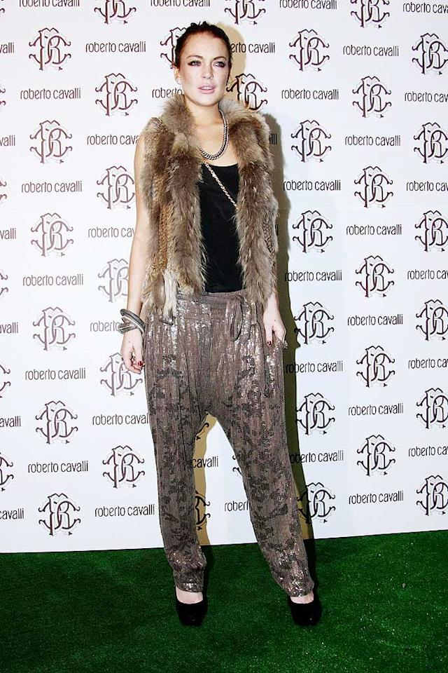 """Lindsay Lohan somehow managed to wrangle an invite to the Roberto Cavalli party in Milan, and she turns up like this? A ratty (hopefully) faux fur vest and sequined fisherman pants that look like they came from the back of grandma's closet won't cut it in Italy, LiLo. LaPresse/<a href=""""http://www.x17online.com"""" target=""""new"""">X17 Online</a> - February 28, 2010"""