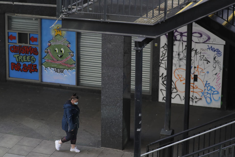 A woman walks by closed shops, in Waterloo in London, Saturday, Jan. 23, 2021 during England's third national lockdown since the coronavirus outbreak began. The U.K. is under an indefinite national lockdown to curb the spread of the new variant, with nonessential shops, gyms and hairdressers closed, and people being told to stay at home. (AP Photo/Kirsty Wigglesworth)