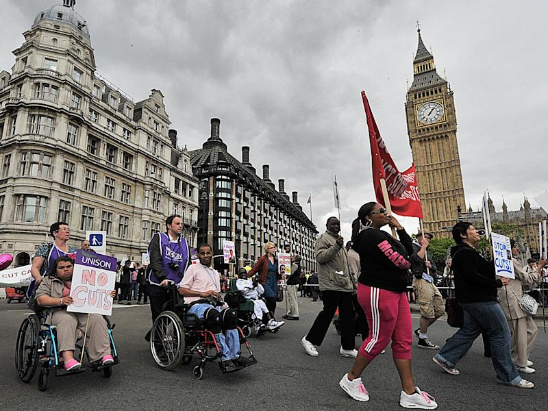 Disability rights protestors demonstrate past the Houses of Parliament, in central London: Getty