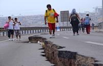 People walk along a cracked road in Iquique, northern Chile, on April 2, 2014 a day after a powerful 8.2-magnitude earthquake hit off Chile's Pacific coast