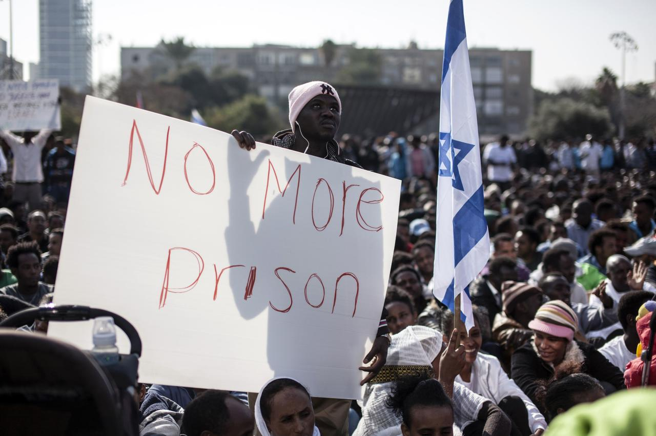 African migrants take part in a protest at Rabin Square in Tel Aviv January 5, 2014. About 10,000 African migrants, largely from Sudan and Eritrea, protested in central Tel Aviv on Sunday against Israel's slow processing of asylum requests and arrests of hundreds under an Israeli law, approved last month and contested by human rights groups, which entitles the authorities to detain migrants lacking valid visas without charges. REUTERS/Nir Elias (ISRAEL - Tags: POLITICS SOCIETY IMMIGRATION CIVIL UNREST)