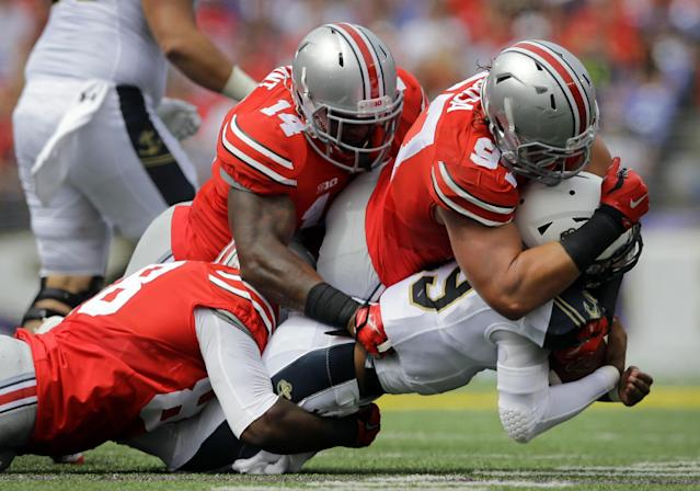 Ohio State defensive lineman Steve Miller, from left, linebacker Curtis Grant and defensive lineman Joey Bosa sack Navy quarterback Keenan Reynolds in the first half of an NCAA college football game in Baltimore, Saturday, Aug. 30, 2014. (AP Photo/Patrick Semansky)