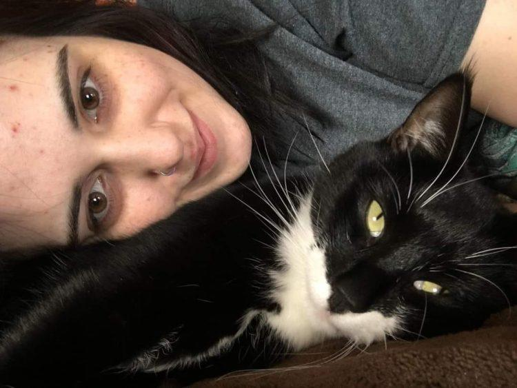 A woman cuddles with a black and white cat