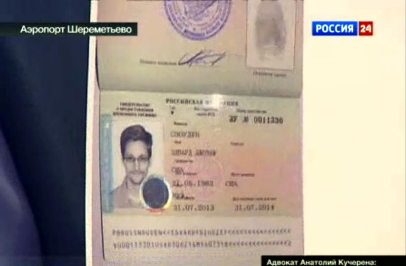 In this image taken form Russia24 TV channel, Russian lawyer Anatoly Kucherena shows Snowden's a temporary document Russia while speaking to the media after visiting National Security Agency leaker Edward Snowden at Sheremetyevo airport outside Moscow, Russia, on Thursday, Aug. 1, 2013. National Security Agency leaker Edward Snowden has received asylum in Russia for one year and left the transit zone of Moscow' airport, his lawyer said Thursday. Kucherena said after meeting with the fugitive at Moscow's Sheremetyevo airport, where he was stuck since his arrival from Hong Kong on June 23, that he handed him the papers proving his status. Kucherena said that Snowden's whereabouts will be kept secret for security reasons. (AP Photo/Russia24 via APTN) TV OUT