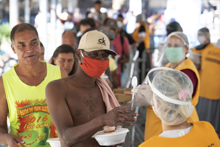 Volunteers from a Christian church serve food to homeless people during a quarantine imposed by the state government to help contain the spread of the new coronavirus in Sao Paulo, Brazil, Monday, April 27, 2020. (AP Photo/Andre Penner)