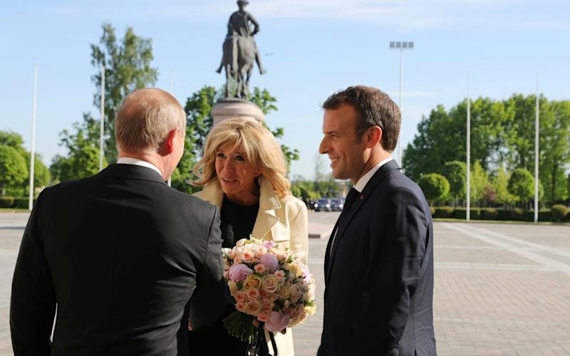 Russian President Vladimir Putin meets with French President Emmanuel Macron and his wife Brigitte Macron in St. Petersburg - REUTERS