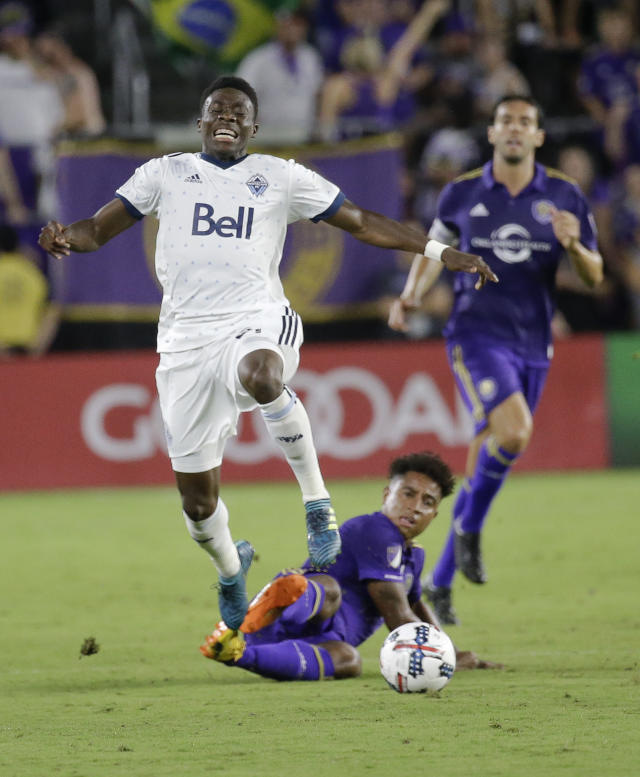In this Saturday, Aug. 26, 2017, file photo, Vancouver Whitecaps's Alphonso Davies, left, leaps over Orlando City 's Cristian Higuita after the two collided going after the ball during the second half of an MLS soccer match in Orlando, Fla. (AP Photo/John Raoux, file)