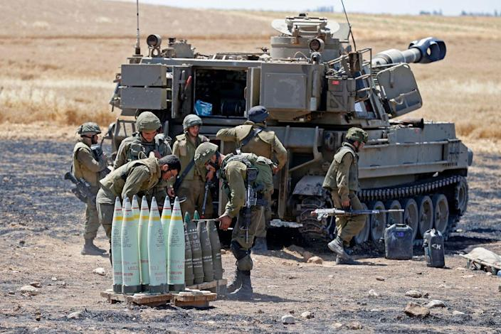 Israeli soldiers stand behind a tank, with artillery shells