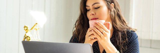 photo of woman in front of laptop with a mug raised to her face